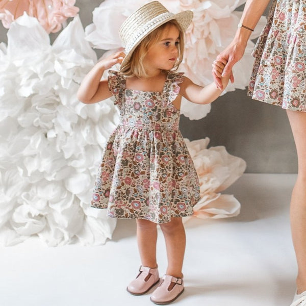 US stockist of Karibou Kids cotton Wild Meadow sunshine dress.  In muted florals, with pretty flutter sleeves, adjustable straps and an open back.