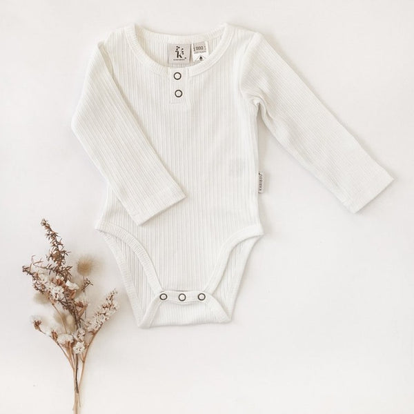 US stockist of Karibou Kids gender neutral, warm white Willow long sleeve henley bodysuit in ribbed cotton blend.