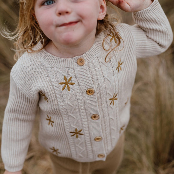 US stockist of Grown Clothing's Flower Field Cable Cardigan.  Made from 100% organic cotton with wooden buttons down front.  Oatmeal color with machine embroidered gold flowers.