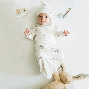 Stockist of Bonsie's rayon blend baby gown in gender neutral white fabric with star print.  Features cross over velcro top that can be undone for skin to skin.  Elastic waist which can be pulled down for easy diaper changes.