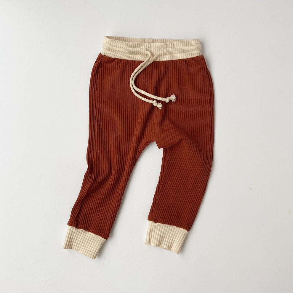 US stockist of Bel & Bow's gender neutral ribbed cotton joggers in rust.  Has a contrasing cream cuffs and waistband with functional drawstring.