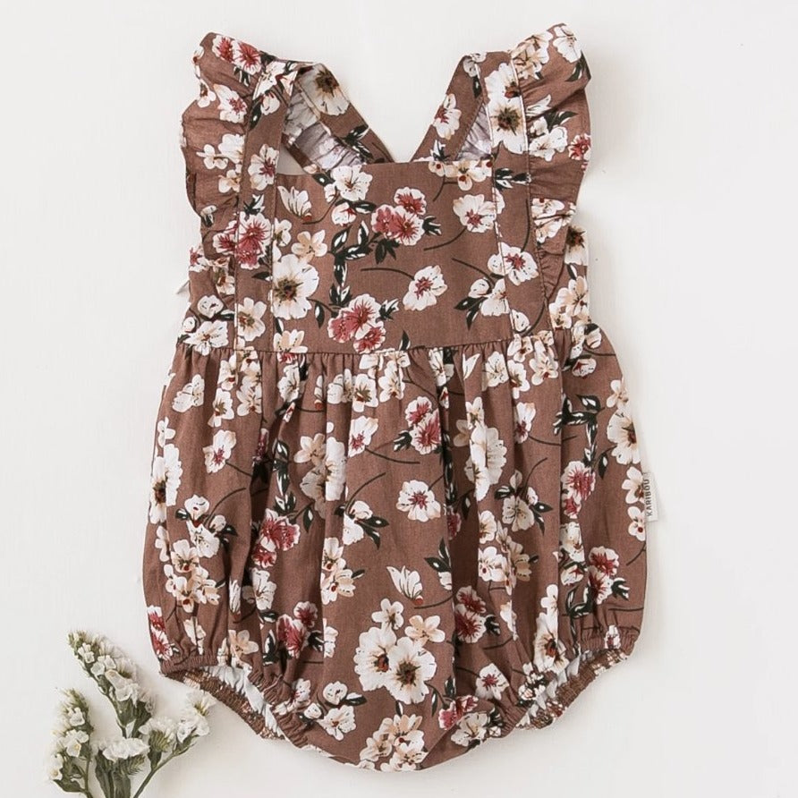 US stockist of Karibou Kids Karolina flower bomb playsuit.  Gorgeous earth tones and pretty florals with flutter sleeves, bow at the back, invisible zip at side and snaps at the crotch.