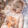 "US stockist of Lacey Lane's short sleeve ""flower child"" bodysuit.  Made from soft apricot jersey fabric, with flower child printed on the front.  Has 3 pearl buttons at back and snaps at crotch."
