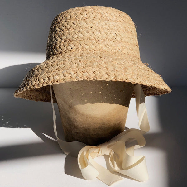 US stockist of Fini the Label's vintage French style straw hat.  Made from raffia straw with a wide bell shaped brim and a trimmed natural ribbon beget chin strap.