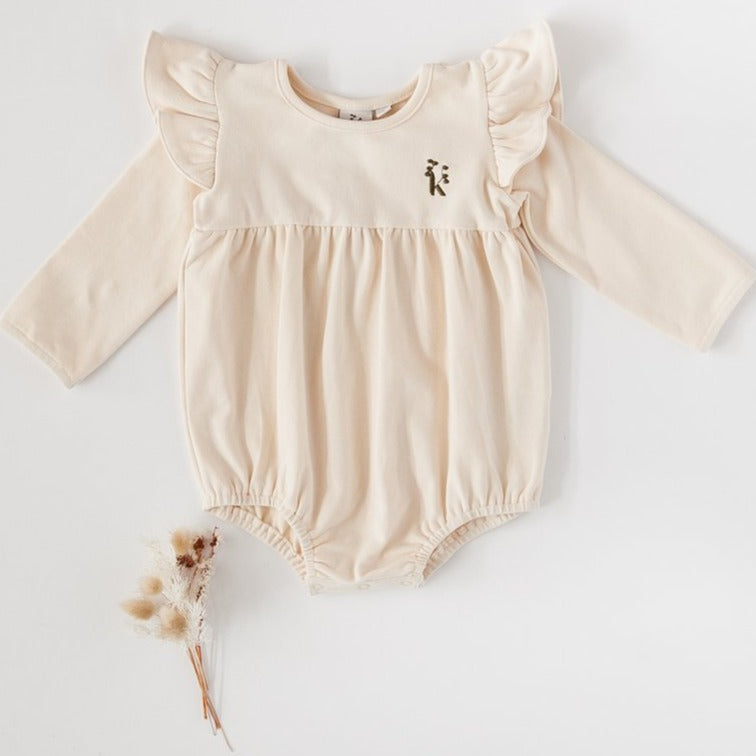 US stockist of Karibou Kid's Milana Winged Playsuit in almond cream.  Made from soft cotton, featuring long sleeves and ruffled wings at shoulders.