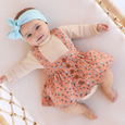 US stockist of Lacey Lane's Peach suspender skirt.  Peach cotton fabric with a pretty design of white and blue flowers.  Features pockets and oversized buttons down front.