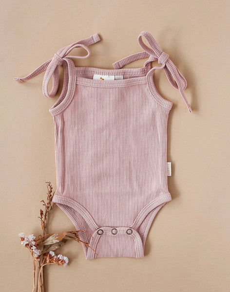 US stockist of Karibou Kids Sienna sunsuit in blush.  Made from cotton in with tie straps at shoulders and snaps at crotch.