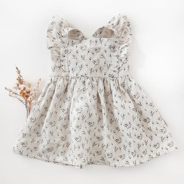 US stockist of Karibou Kid's My Little Sunshine Dress in Antique Bronze Cotton Puff Print.  Made from a oatmeal linen, fully lined with adjustable straps, flutter sleeves and tie bow at back.