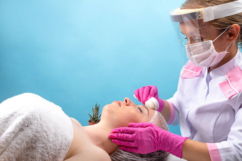 Facial spa safety, woman wearing face shield while giving a young woman a facial massage