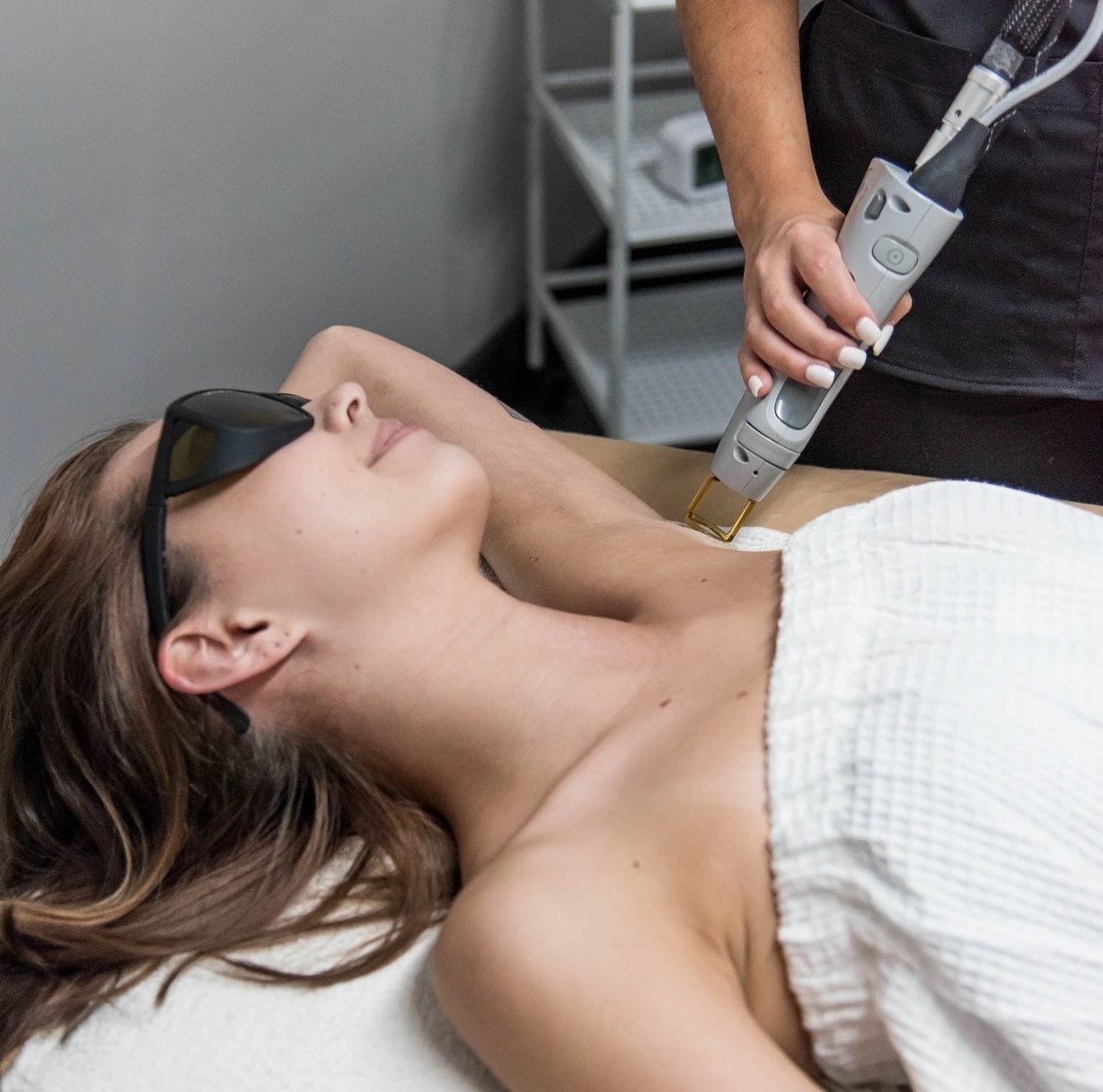 A woman receiving laser hair removal treatment under arms