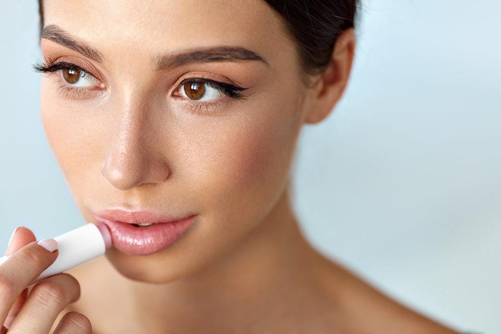Woman using hyaluronic acid lip booster as an alternative to lip injections