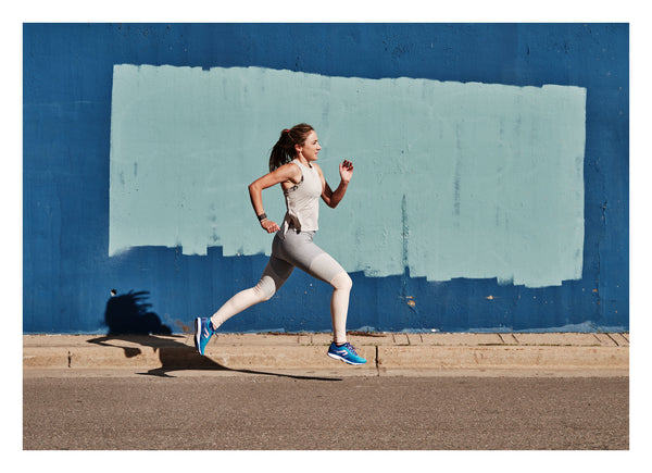 Woman running in the Newton Running Fate 7
