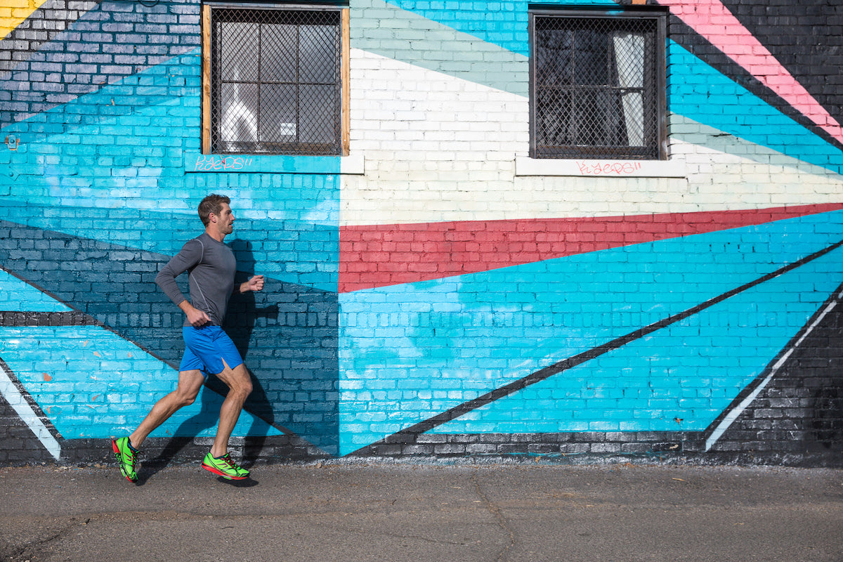 Man running outside against a patterned wall wearing Newton shoes