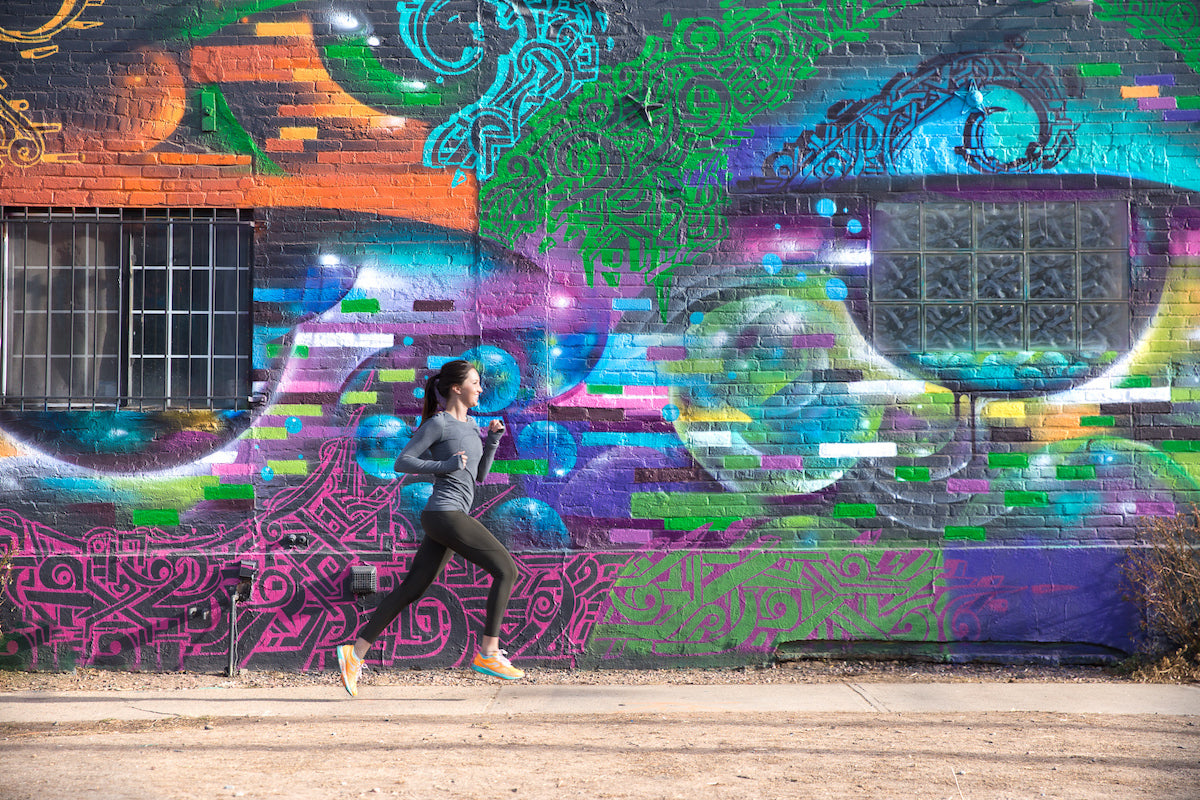 Woman running outside against a patterned wall wearing Newton shoes