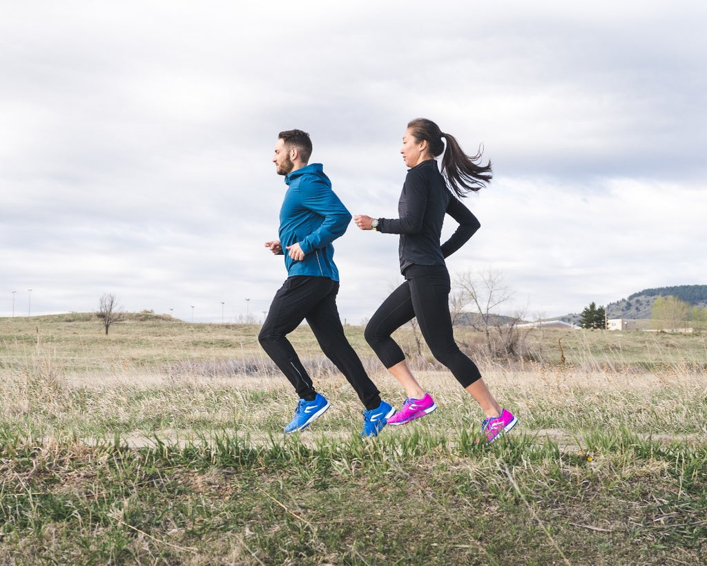 Man and woman running in the Newton Kismet 5
