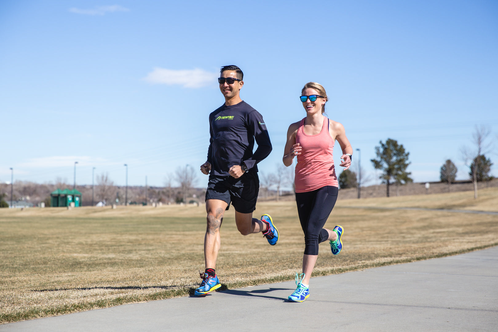 Man and woman running outside on a path wearing Newton Fate 4 shoes