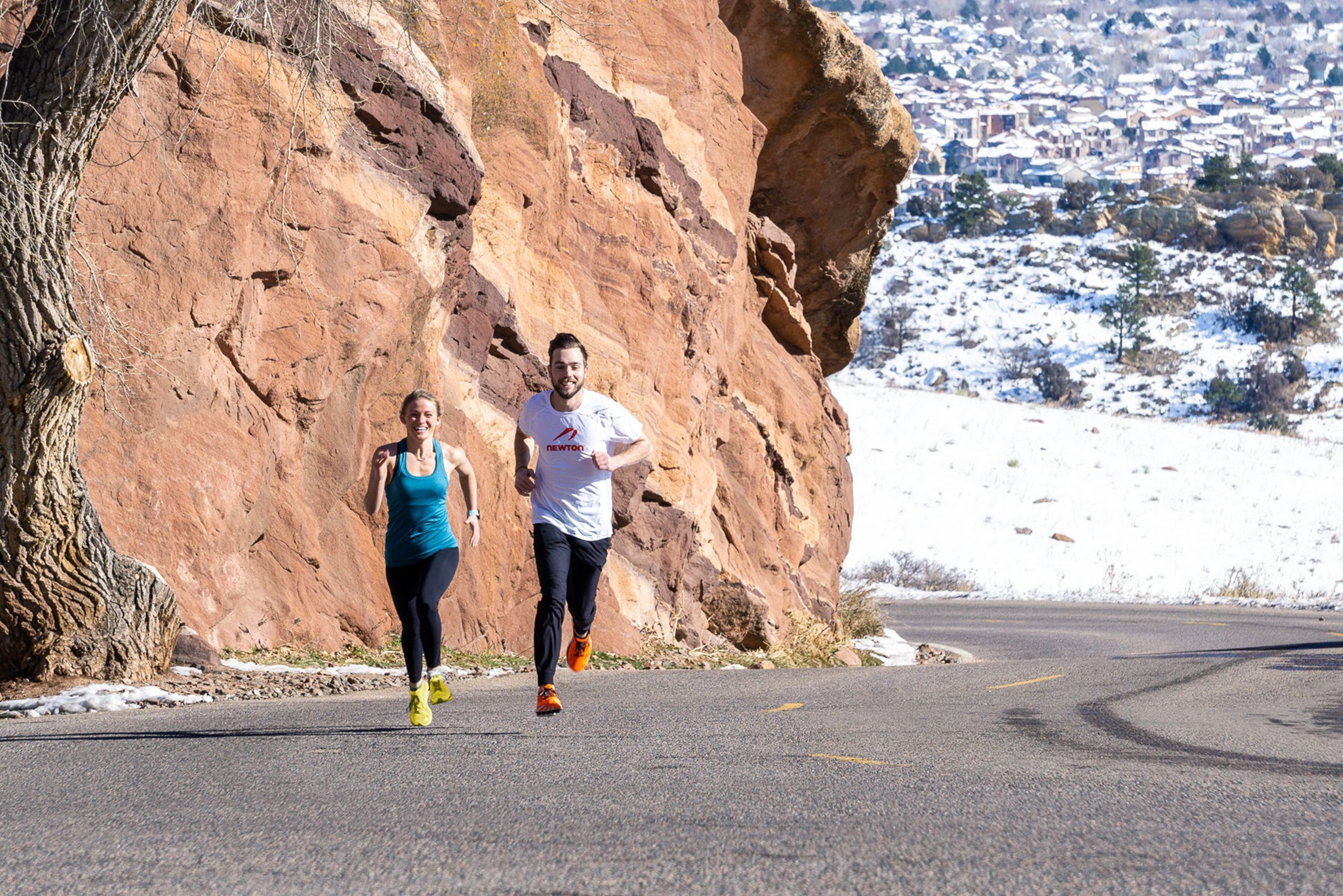 Couple running outside on a path wearing Newton shoes