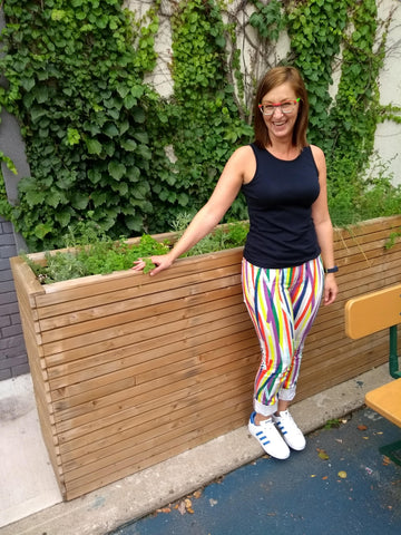 Sarah laughing in front of a flower box in colourful pants