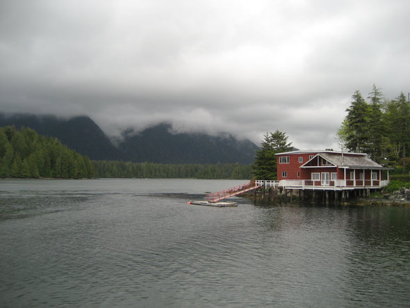 red house on the water with fog lifting
