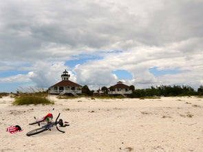 a view of the port boca grande lighthouse museum from the beach, with a bicycle and towel in the foreground