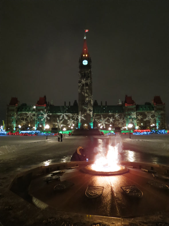 christmas lights on parliament hill with the eternal flame burning in the forefront