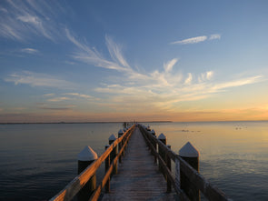 a pier on the gulf of mexico with the setting sun