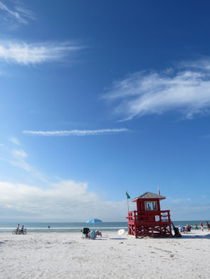 bright blue skies, whispy clouds and white clouds with red lifeguard stand on siesta key, florida