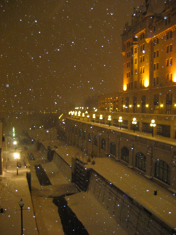 lights shining on the chateau laurier and snow falling on the ottawa rideau canal locks