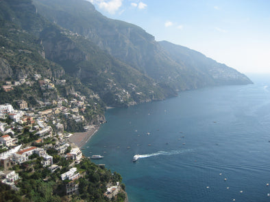 a boat approaching the coast of positano, italy and the cliffs of the amalfi coast