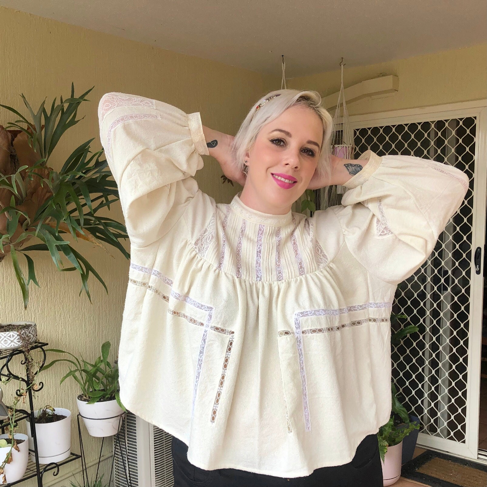 Shannon poses with her hands behind her head whilst smiling at the camera, showing the lace panel details across the front of her Gibson Girl Blouse