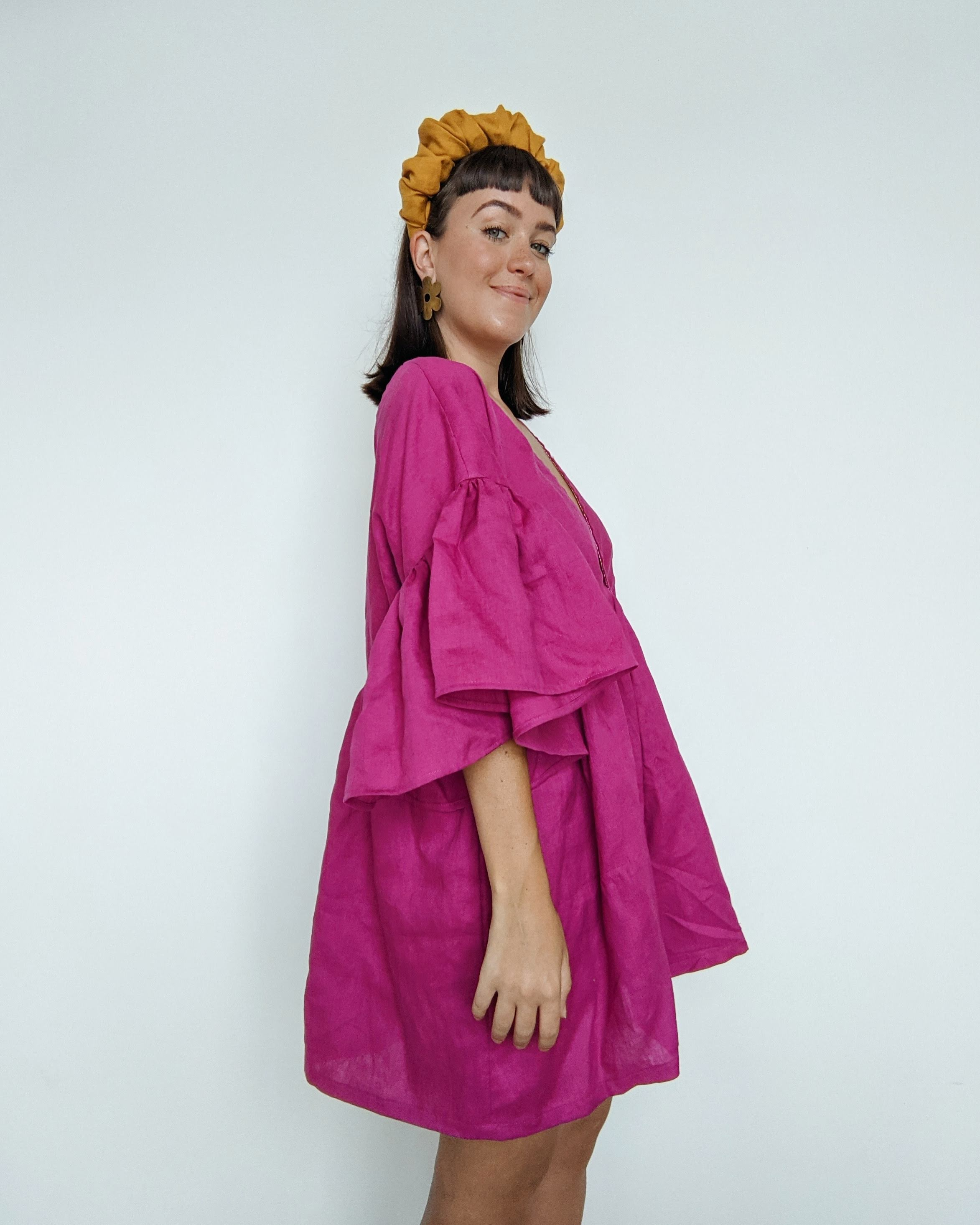 Daisy stands side on smiling towards the camera.  She is wearing a magenta pink linen dress with a golden linen headband.