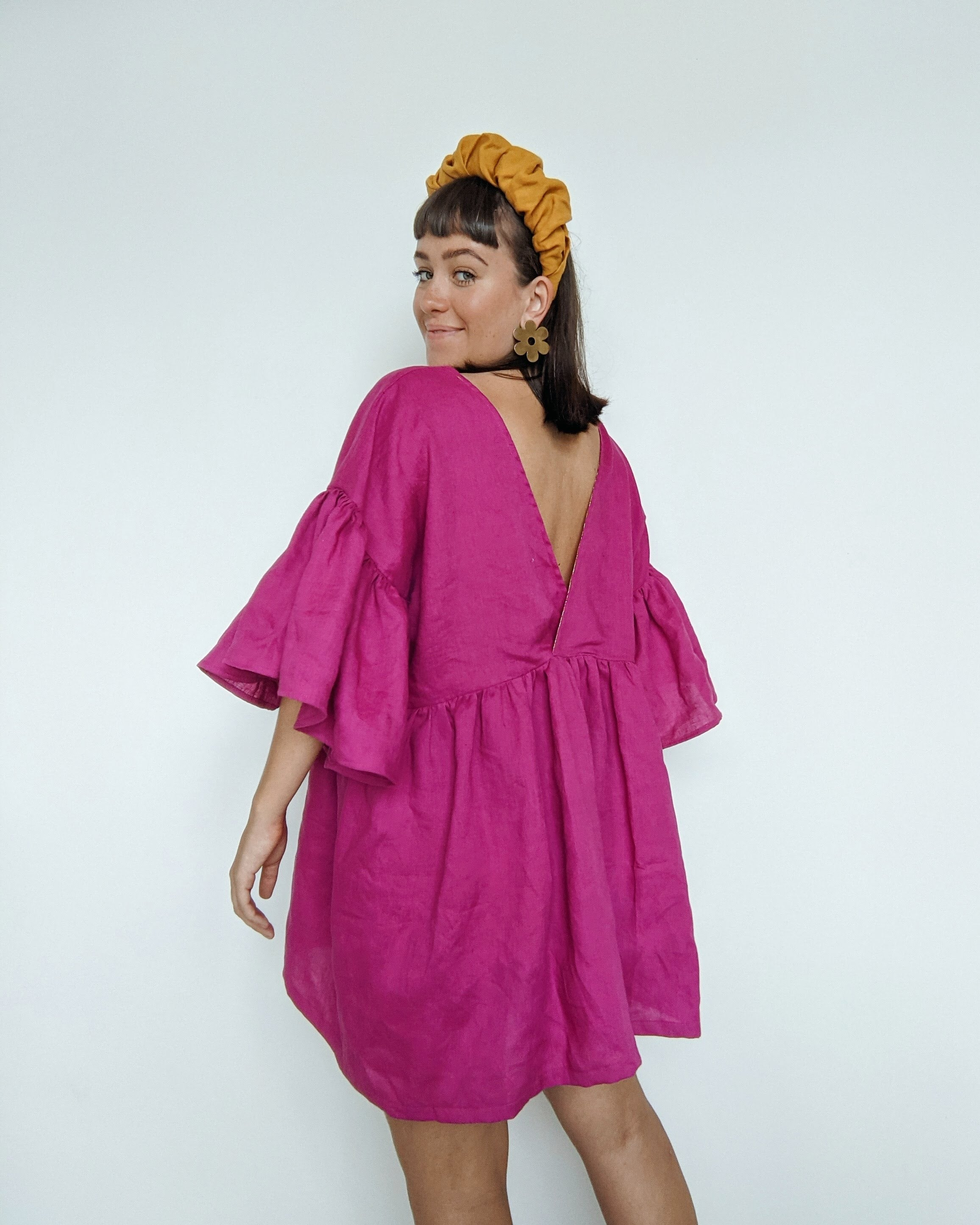Daisy stands with her back facing to show the v back on her magenta linen Maya ruffle dress hack.