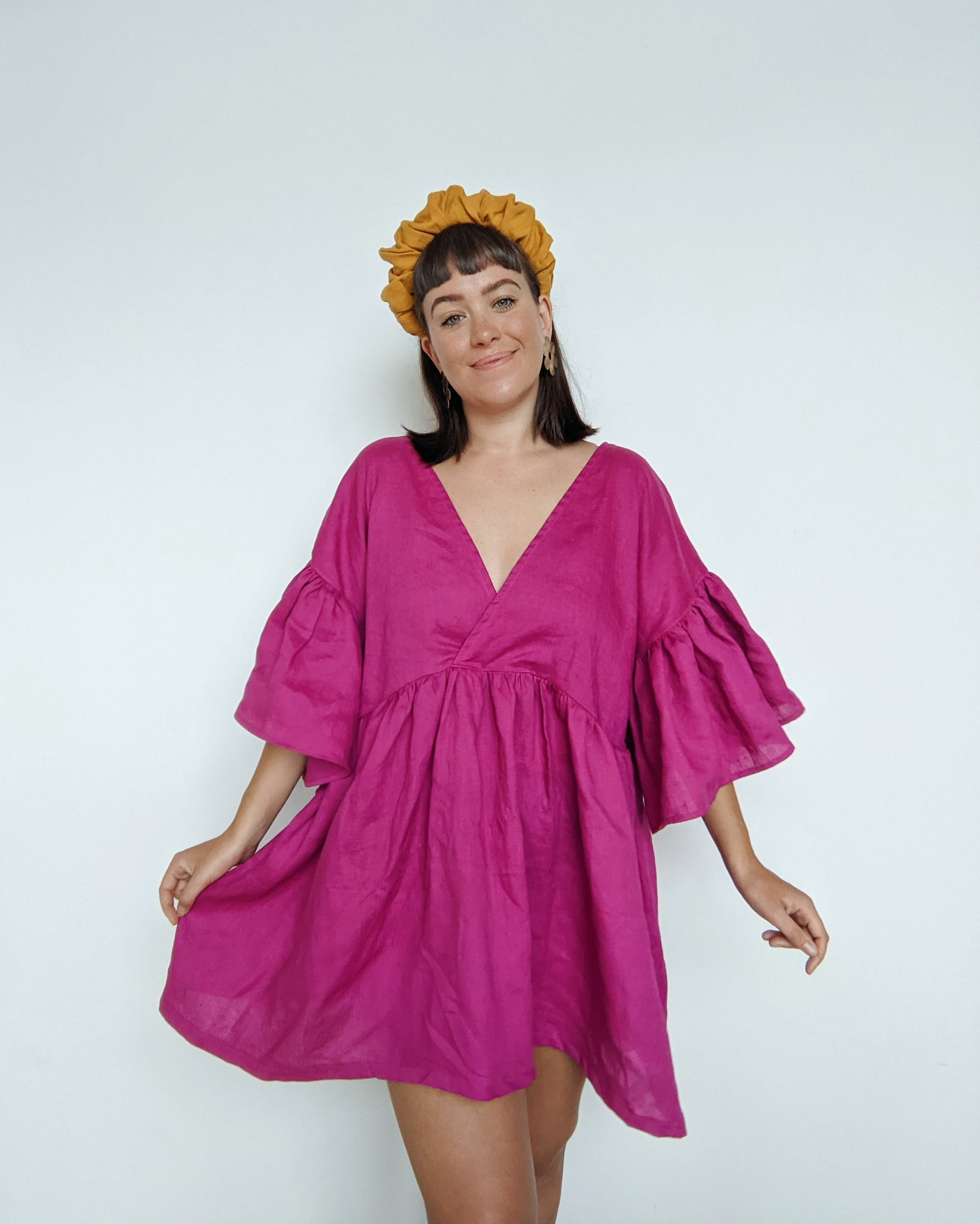 Daisy wears a vibrant, bright pink linen dress with a golden fabric crown headband.  She is holding one side out slightly to show the volume in the Maya ruffle dress skirt.