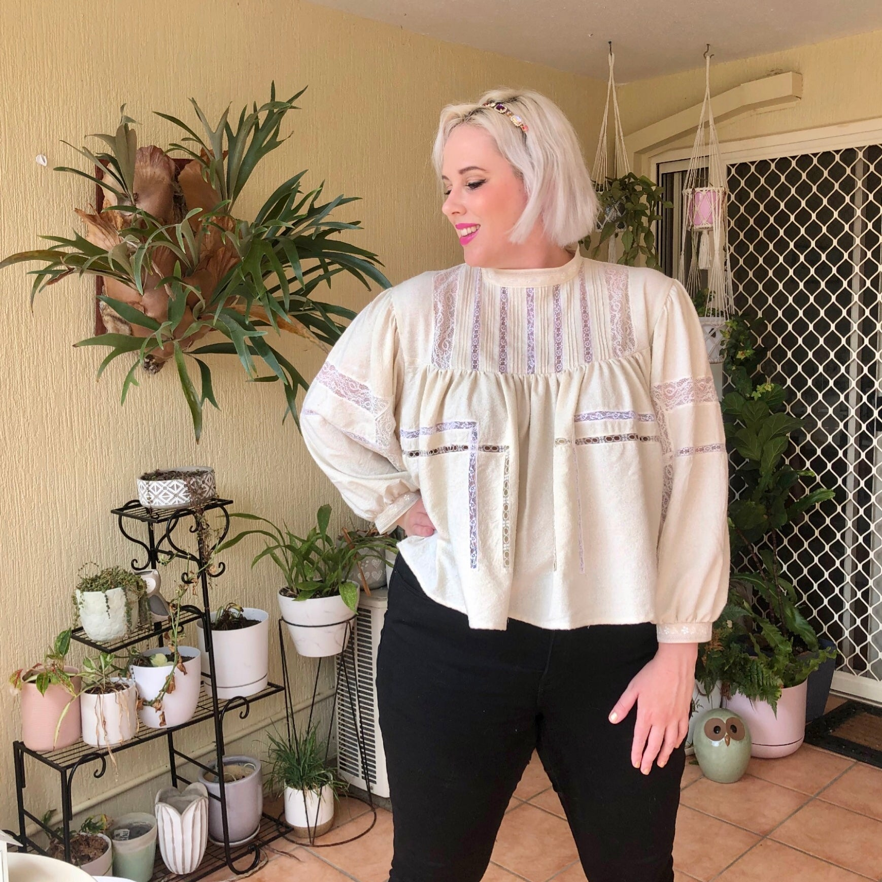Shannon stands with one hand on her hip in front of her potted plants wearing her off white Silk Noil and lace long sleeved blouse with black jeans.  She is looking off to the side.