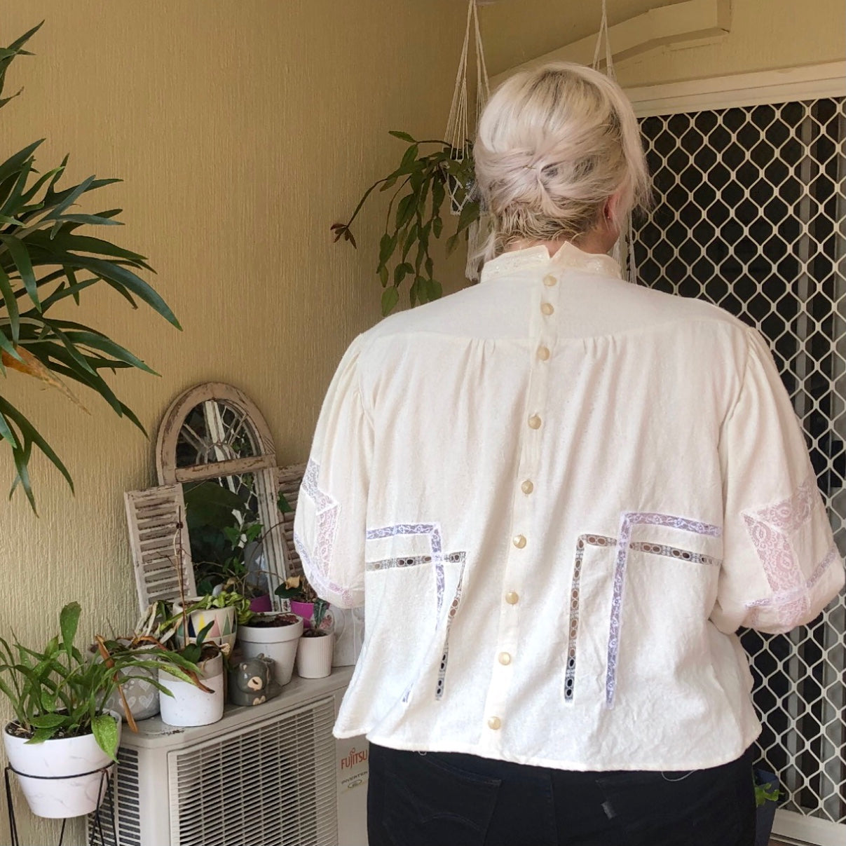 Shannon stands facing away from the camera to show the back details of her Gibson Girl blouse