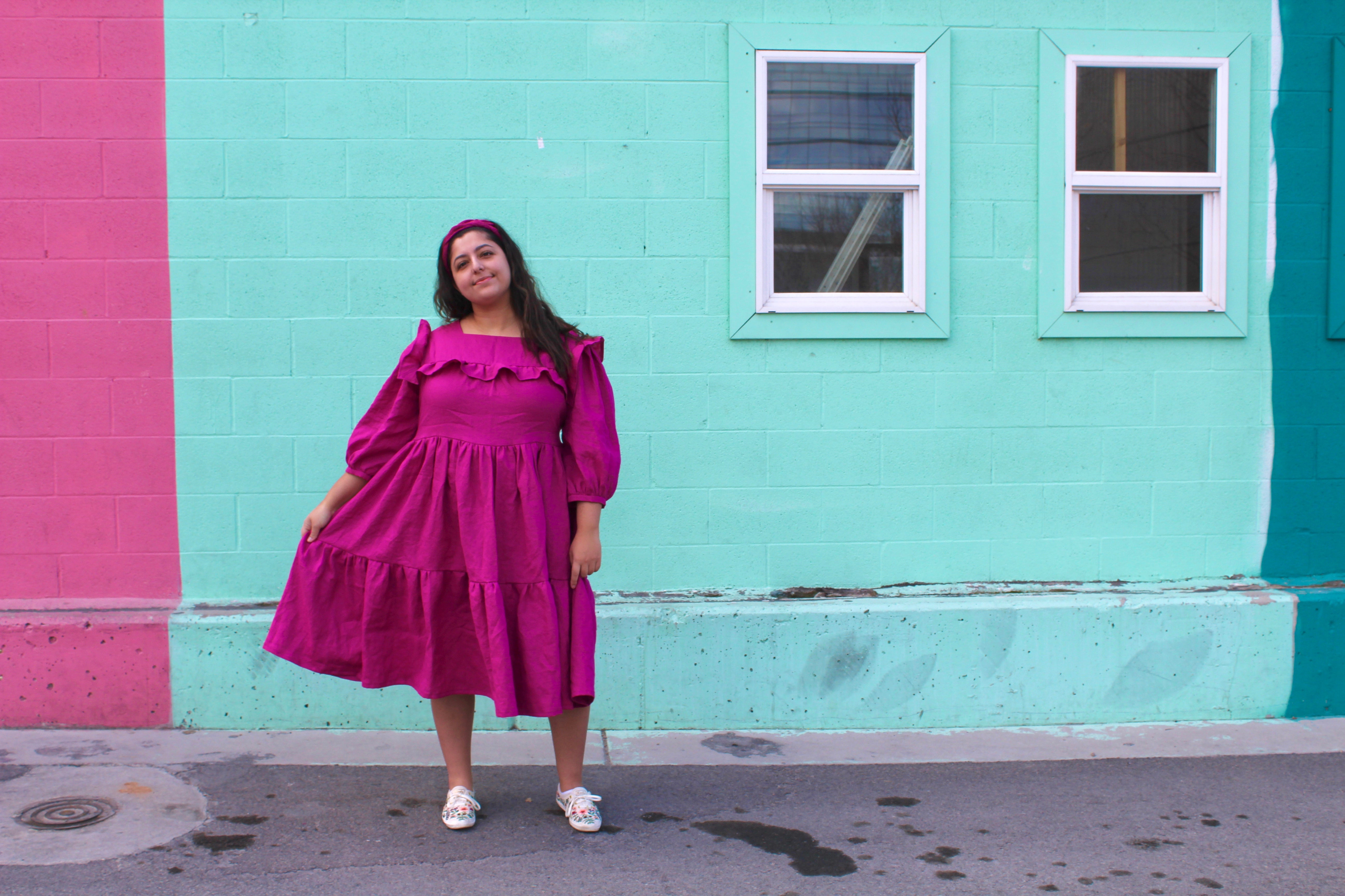 Romy wears a bright pink linen handmade dress, holding one side out slightly from her body to show the vlolume in the tiered skirt.  She is standing in front of a light blue, minty  painted wall.