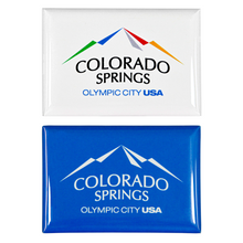 Load image into Gallery viewer, 2 rectangular, shiny magnets. Both have printed artwork. One includes a full colored Colorado Springs: Olympic City USA logo on a white background, and the other is the same logo white on top of a blue background.