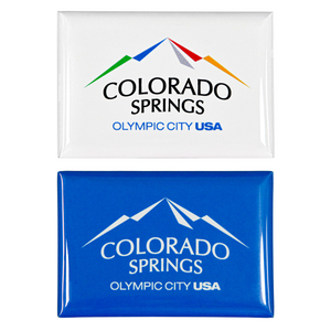 2 rectangular, shiny magnets. Both have printed artwork. One includes a full colored Colorado Springs: Olympic City USA logo on a white background, and the other is the same logo white on top of a blue background.