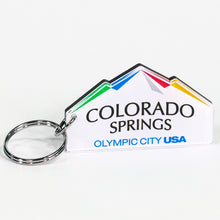 Load image into Gallery viewer, Custom cut keychain of the city of Colorado Springs: Olympic City USA logo. Silver-colored key ring attached. Custom cut to look like mountains.
