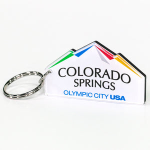Custom cut keychain of the city of Colorado Springs: Olympic City USA logo. Silver-colored key ring attached. Custom cut to look like mountains.