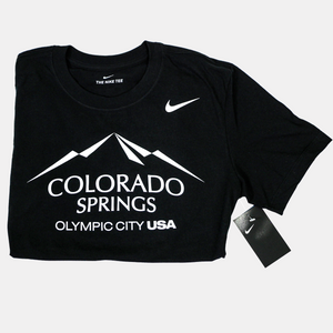Folded in half black short sleeve T-shirt with a white version of the city of Colorado Springs: Olympic City USA logo screen printed onto it. White Nike logo printed underneath the shoulder.
