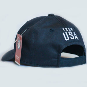 Back view of navy baseball hat. Team USA is embroidered above the closure of the hat.
