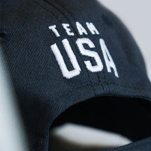 Up close view of the back closure of a navy baseball hat with Team USA embroidered just above the closure
