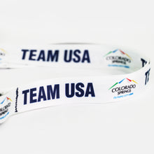 Load image into Gallery viewer, Up close view of the with official City of Colorado Springs: Olympic City USA and Team USA logos and wordmarks decorating a white lanyard