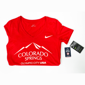 Folded in half horizontally red short sleeve v-neck t-shirt with white version of the city of Colorado Springs: Olympic City USA logo printed on front. White Nike logo under right shoulder. Team USA and Nike tags attached to right sleeve.