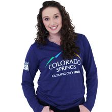 Load image into Gallery viewer, Model wearing dark blue long sleeve v-neck shirt. Shirt has full color logo for the city of Colorado Springs: Olympic City USA printed on front. Team USA printed in white on the left sleeve on the upper arm.