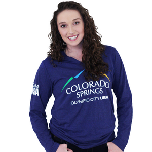 Model wearing dark blue long sleeve v-neck shirt. Shirt has full color logo for the city of Colorado Springs: Olympic City USA printed on front. Team USA printed in white on the left sleeve on the upper arm.
