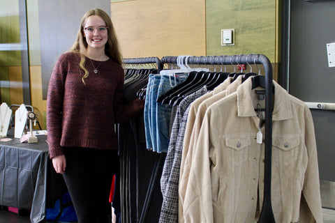 Chloe Fulton, owner of Bloom Boutique, stands beside a rack of her current clothing stock at a local market