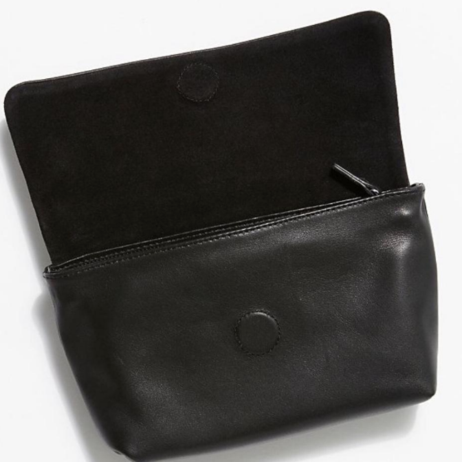Interior view: This versatile bag is crafted from soft black cow leather. Featuring an adjustable and detachable leather strap, meaning it can serve as a clutch, sling or belt bag. Top flap has a magnetic closer with a zipper underneath. 100% polyester lining.