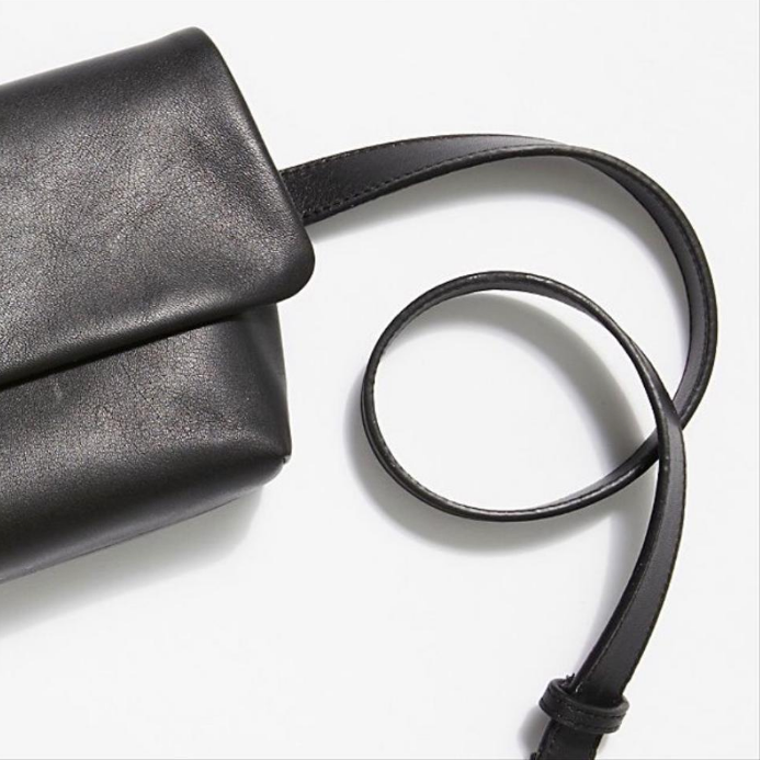 Detail view: This versatile bag is crafted from soft black cow leather. Featuring an adjustable and detachable leather strap, meaning it can serve as a clutch, sling or belt bag. Top flap has a magnetic closer with a zipper underneath. 100% polyester lining.